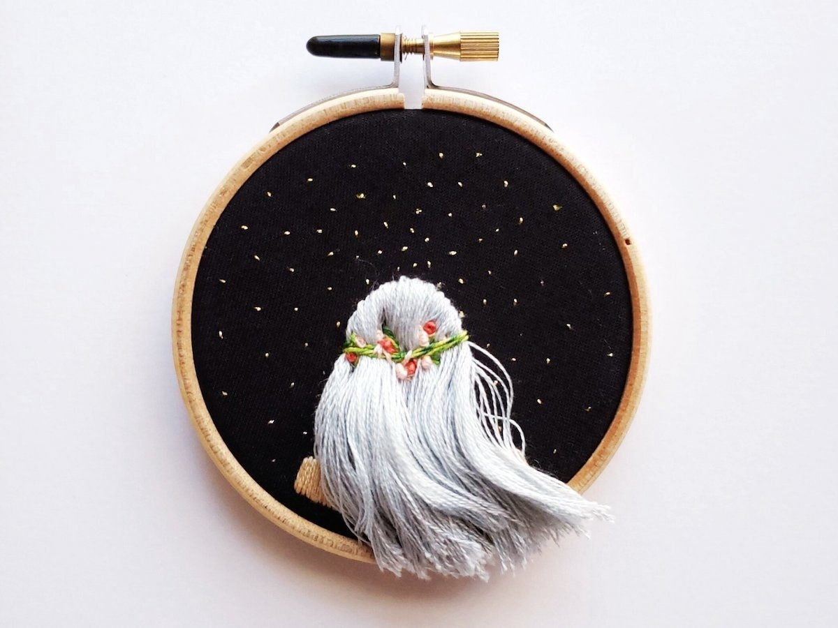 Embroidery hoop art from Desert Eclipse Studio featuring the back of a girl's head as she looks at the stars.