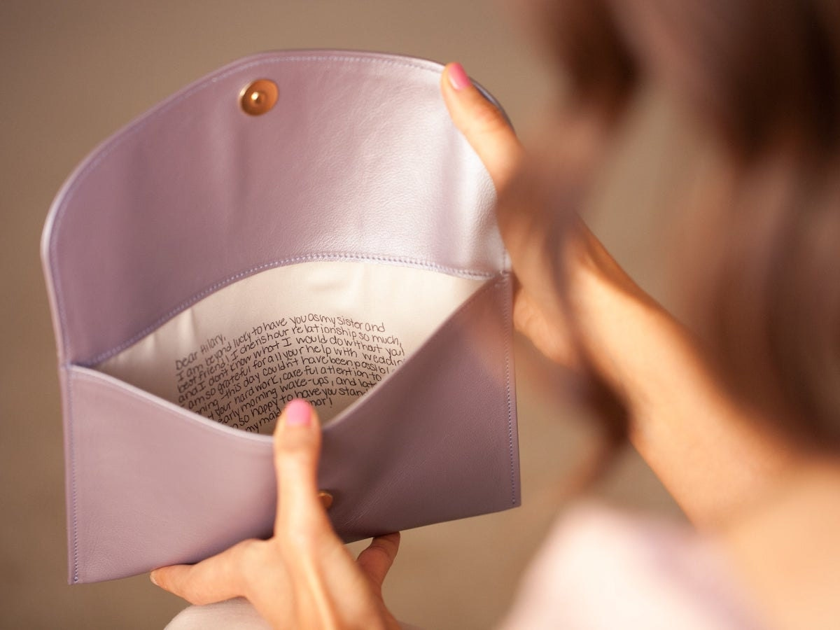 A woman holds open a personalized clutch from Fontém, reading the note inside.