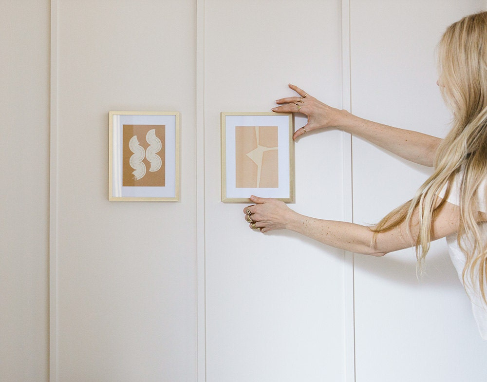 Sarah hangs a small framed art print on the wall, next to another similar design.