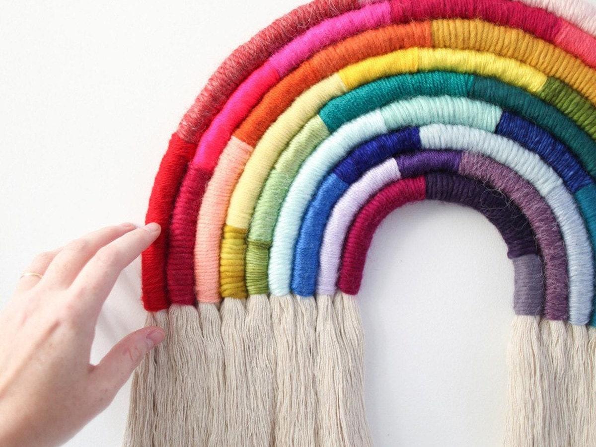 A model touches a fiber art rainbow.