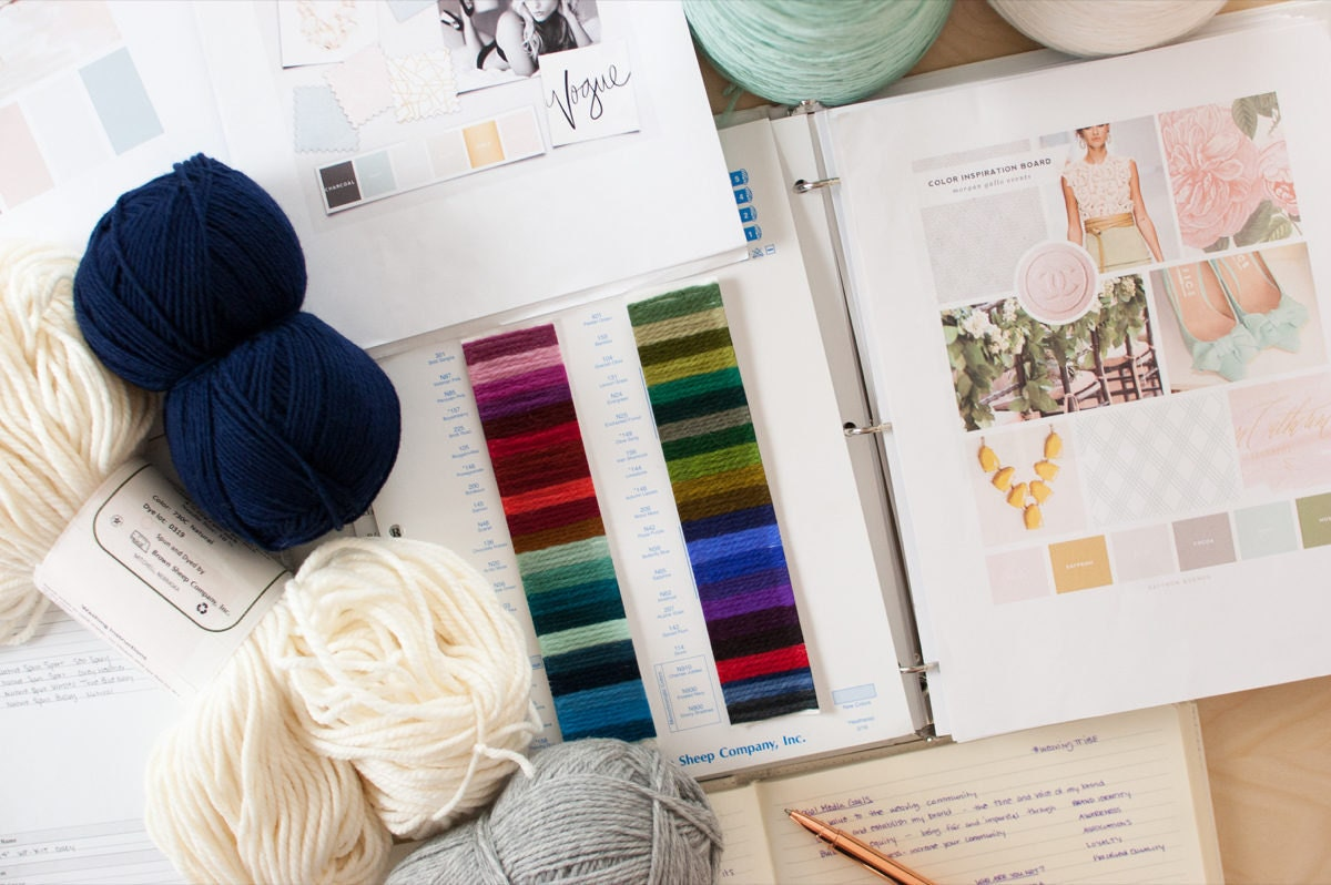 A flat-lay of yarn and color swatches alongside mood boards crafted from magazines.