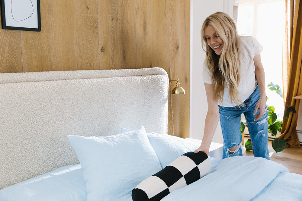 Sarah puts a checkered bolster pillow on her sky blue bed.
