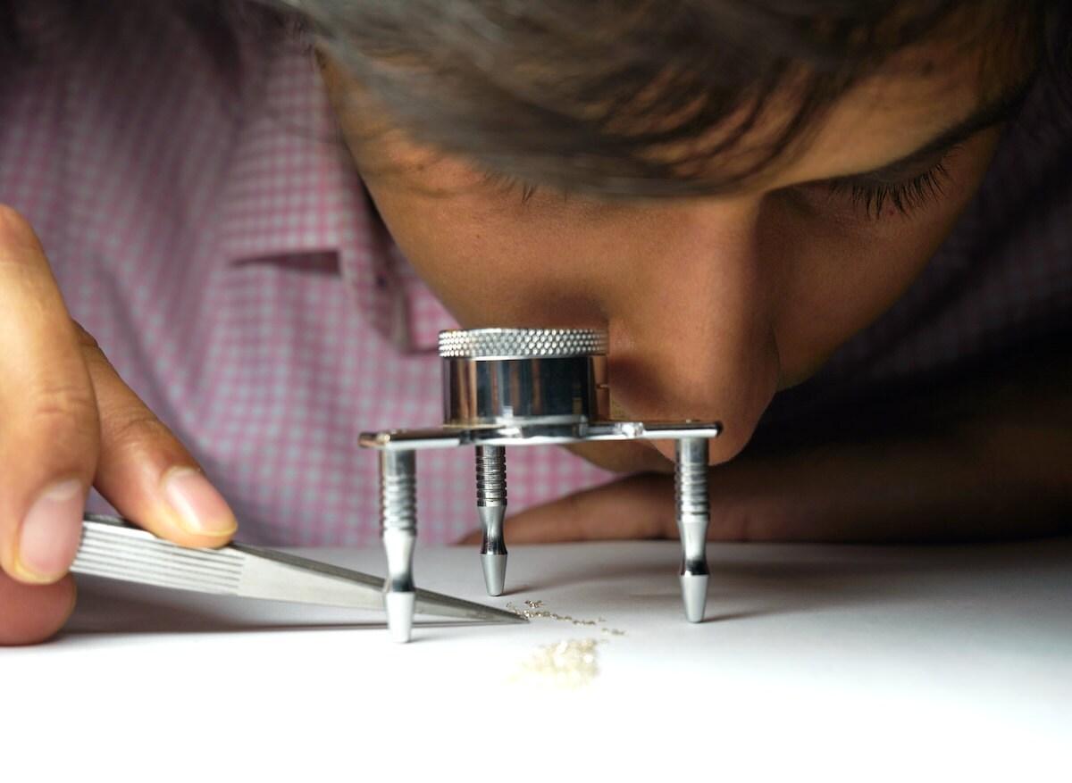 Abhishek examines stones under a magnifying glass