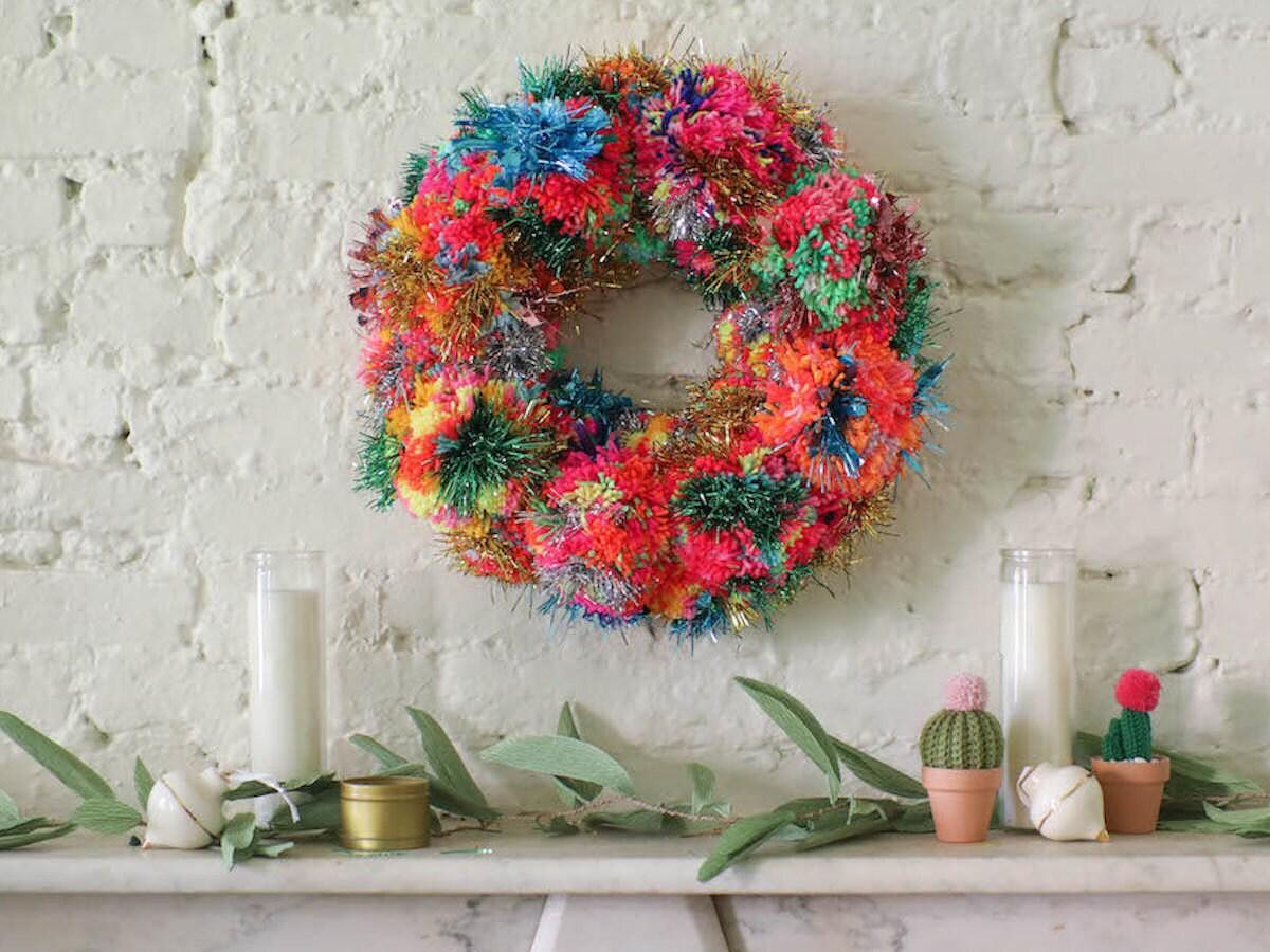 Rainbow pom-pom and tinsel wreath hangs above a mantel
