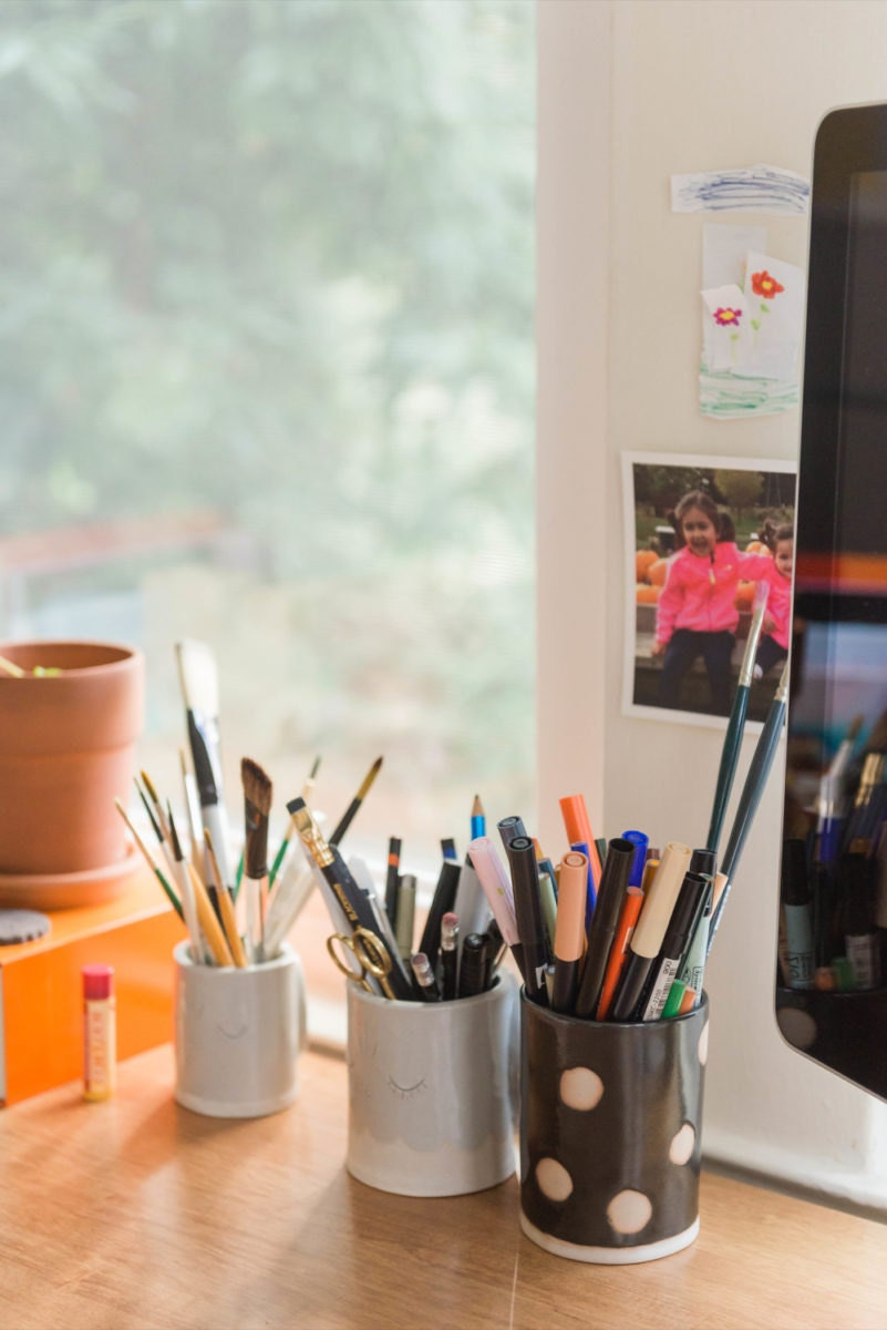 Meenal's tools organized on her desk, including pens, markers, pencils, and paintbrushes