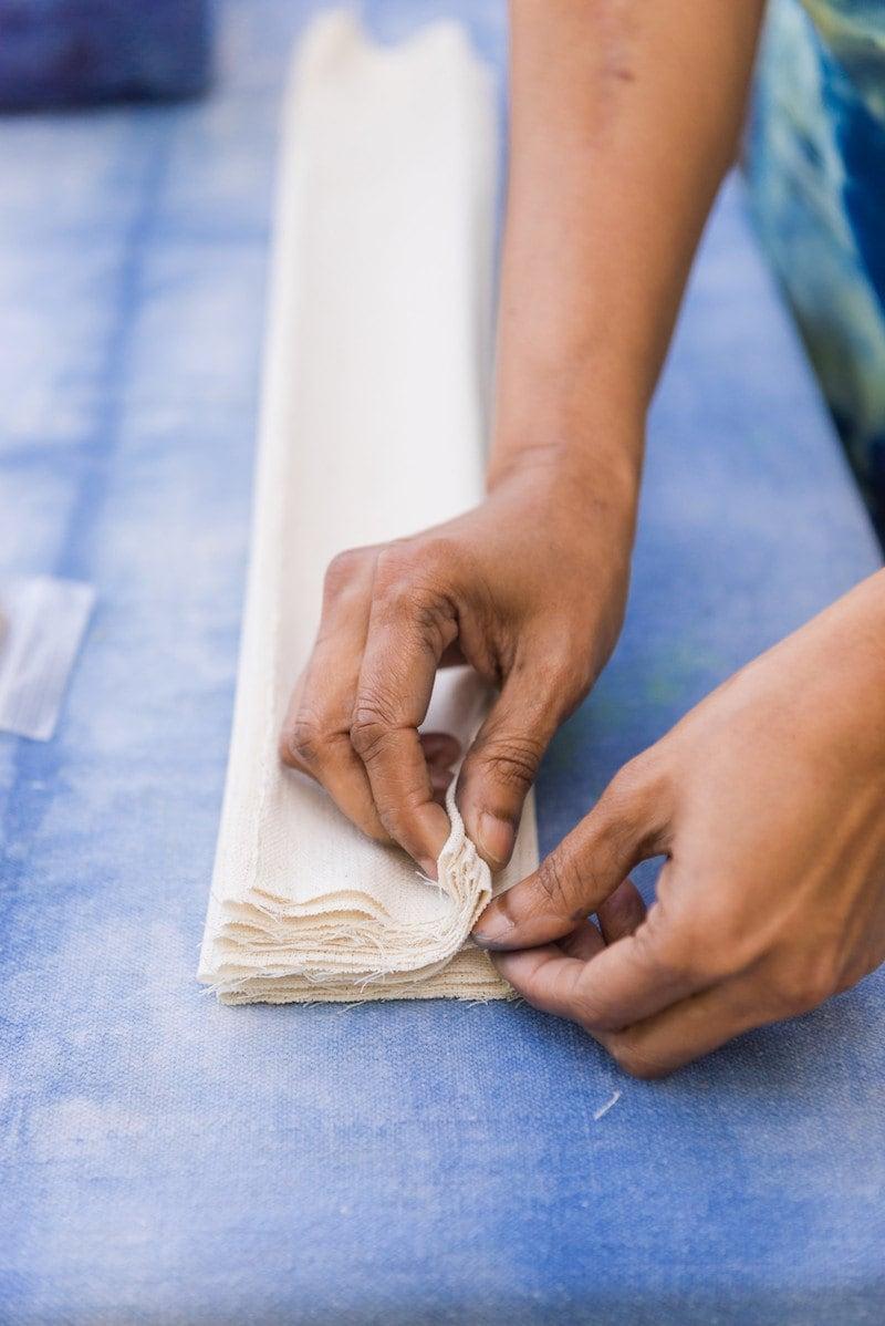 Adroit proprietor Rajni folds a long strip of fabric