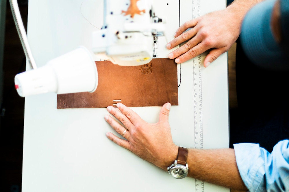 A Holtz Leather Co. employee works on stitching a leather wallet together.