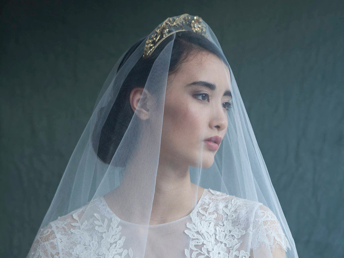 Woman modeling a gold bridal headpiece and veil from Agnes Hart