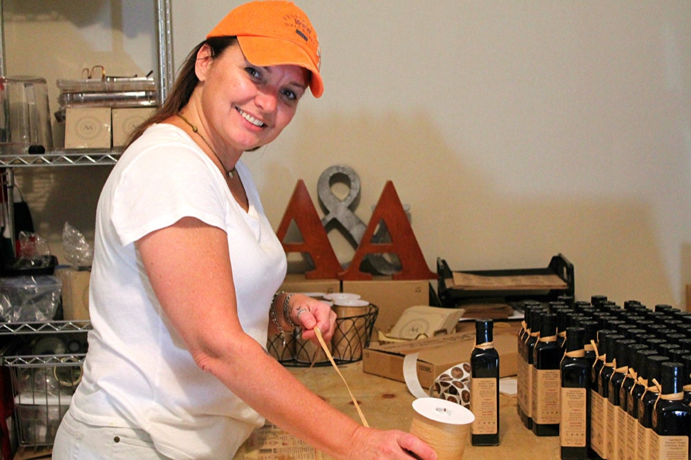 Adriana at work labeling her bottles of balsamic