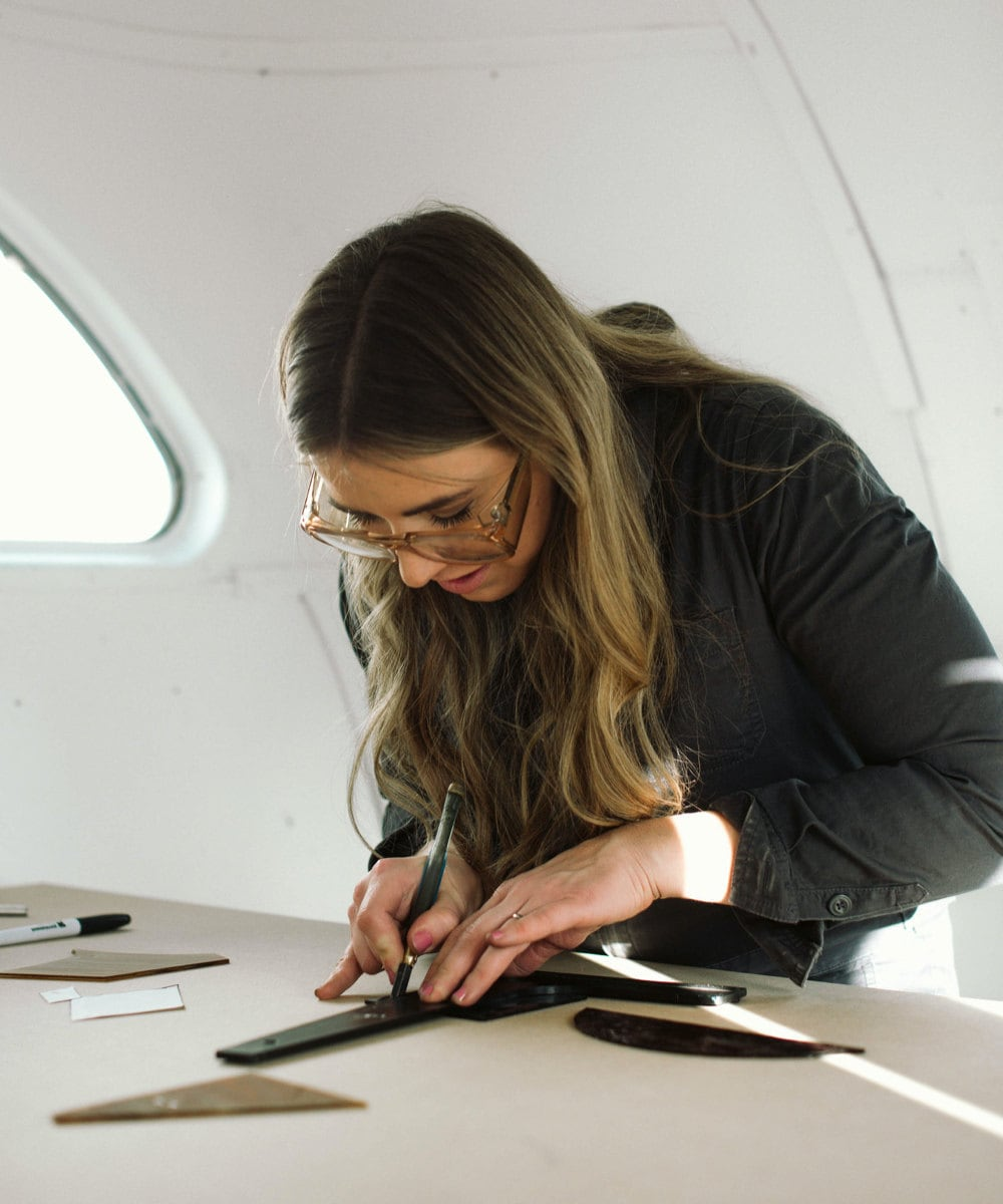 Lauren measures pieces of glass to make a precise cut.