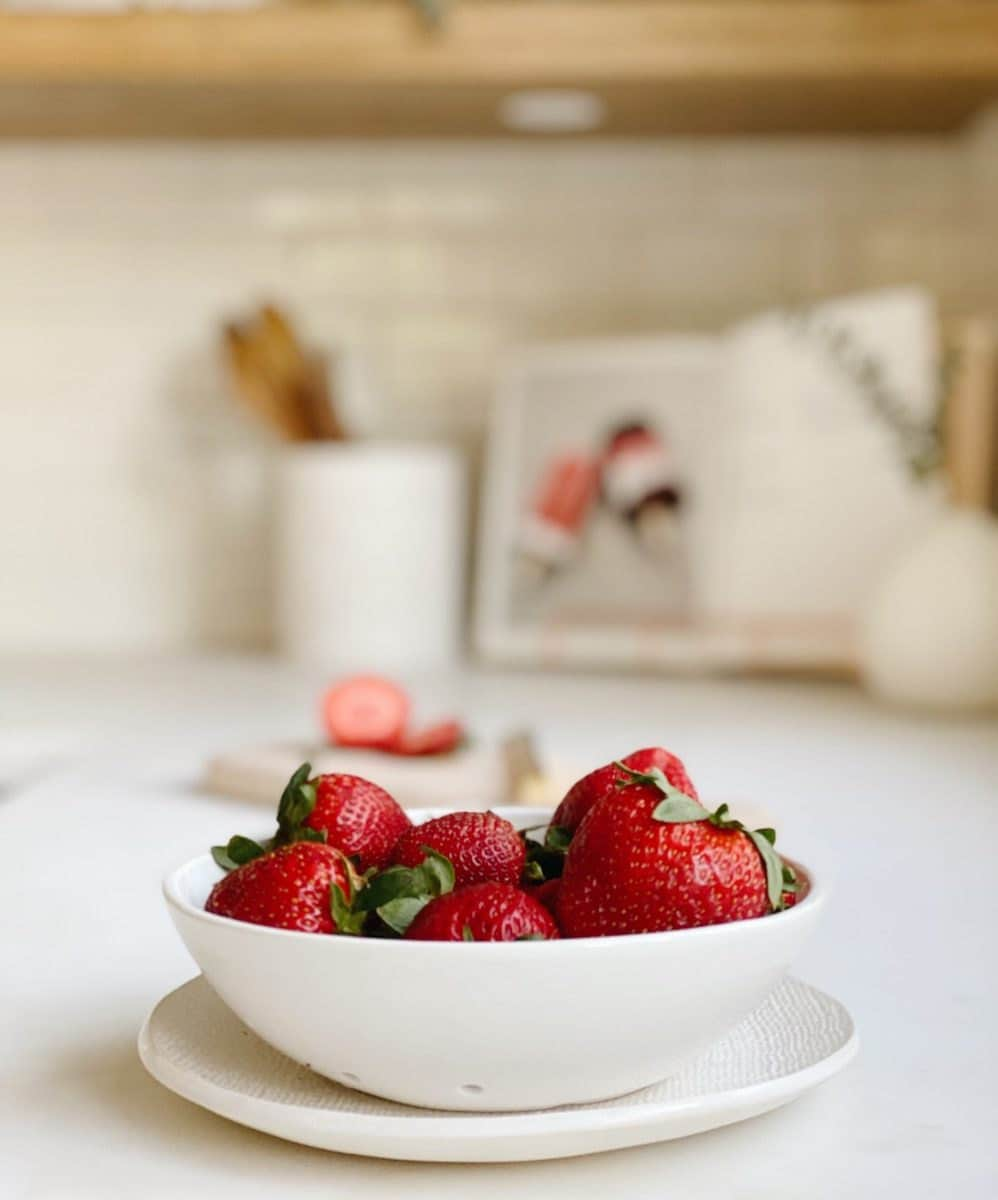 A ceramic berry bowl from lookslikewhite, holding a fresh batch of strawberries.