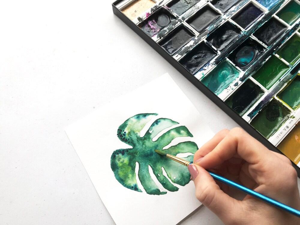 Mica paints a botanical watercolor.