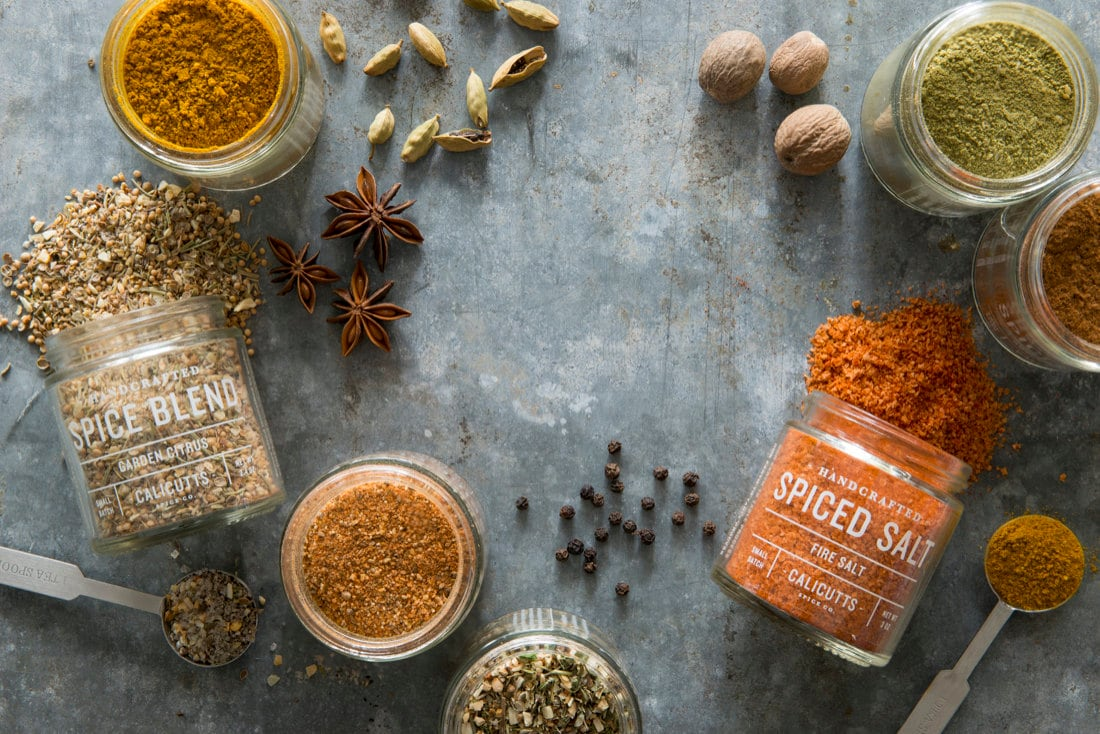 Jars of Calicutts Spice Co. blends pictured alongside the whole seeds that are used to make them.