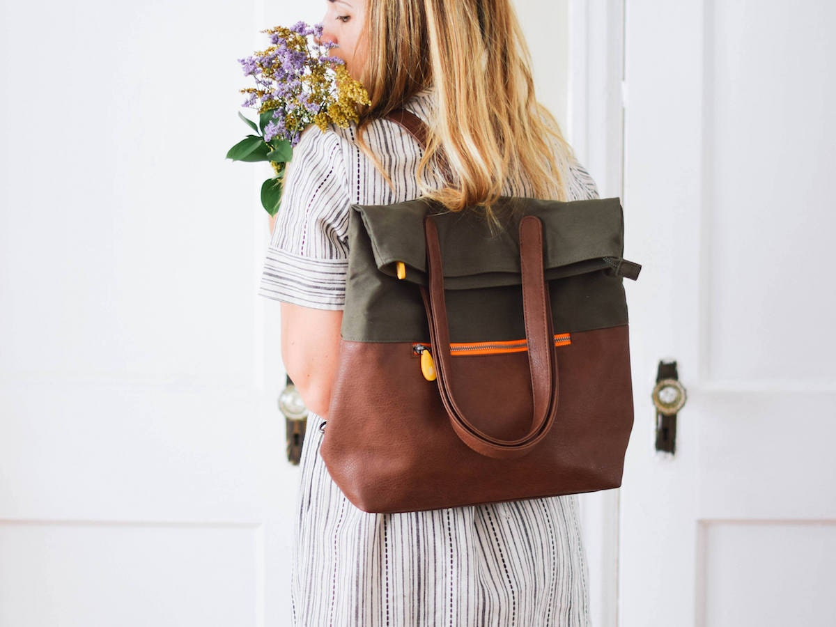 Woman wearing convertible vegan leather backpack from Canopy Verde in olive green and espresso.