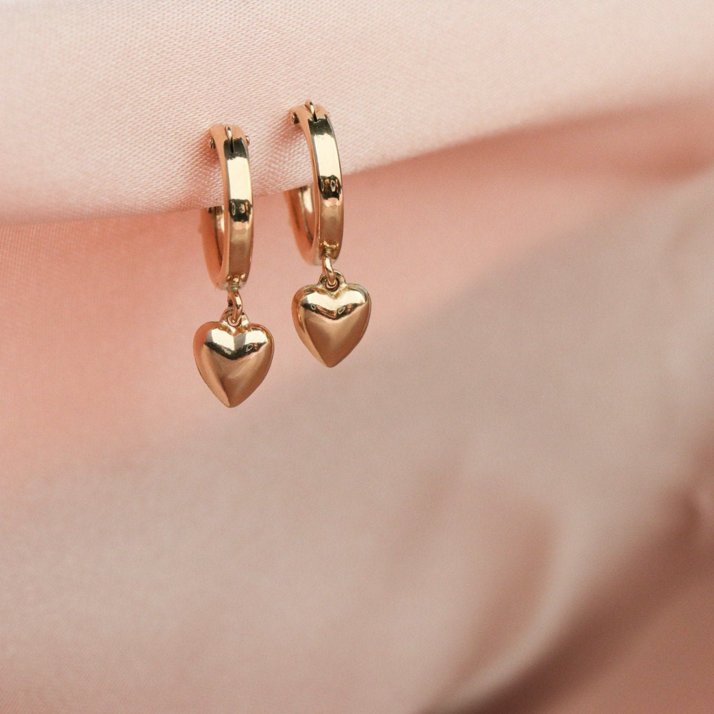 A set of tiny gold drop earrings shaped like hearts from EVREN.