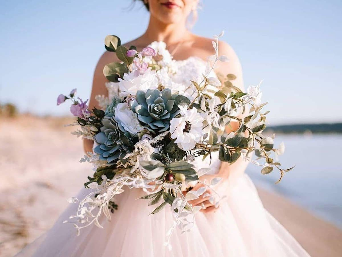 A real Faux Bouquets bride holds a succulent bouquet on the beach