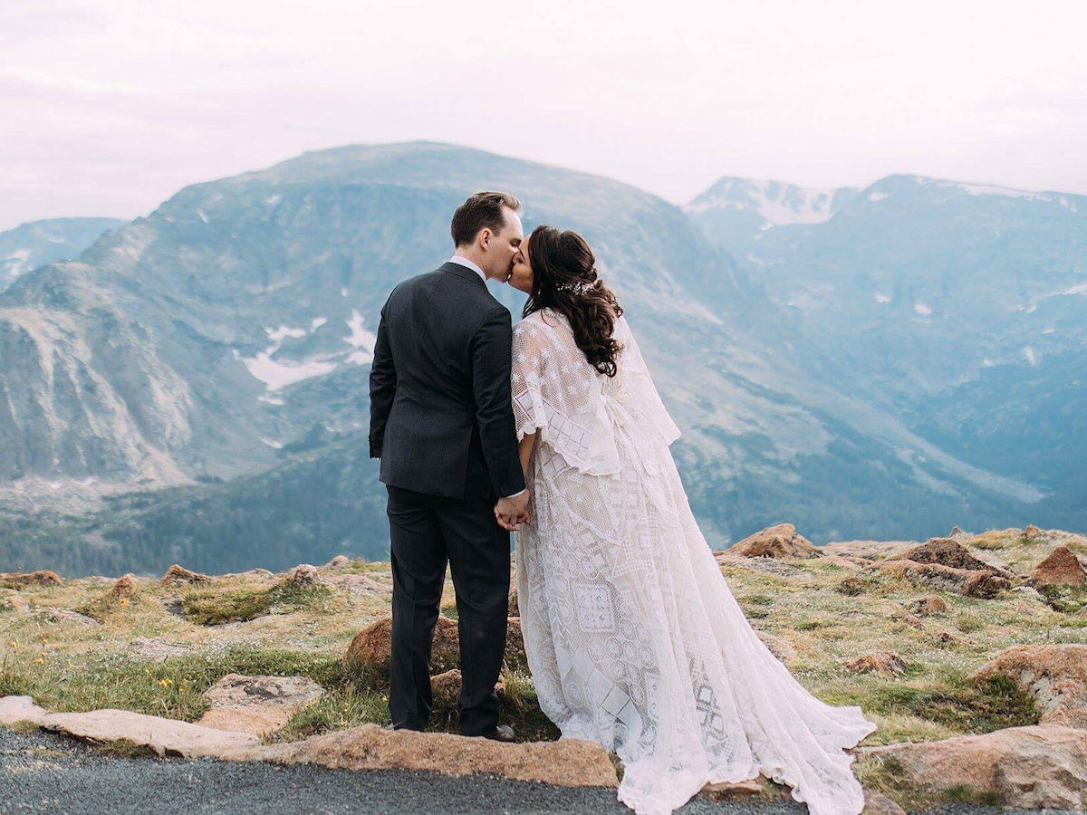 A bride wearing a wedding dress by Reclamation kisses her groom in front of a scenic mountain backdrop.