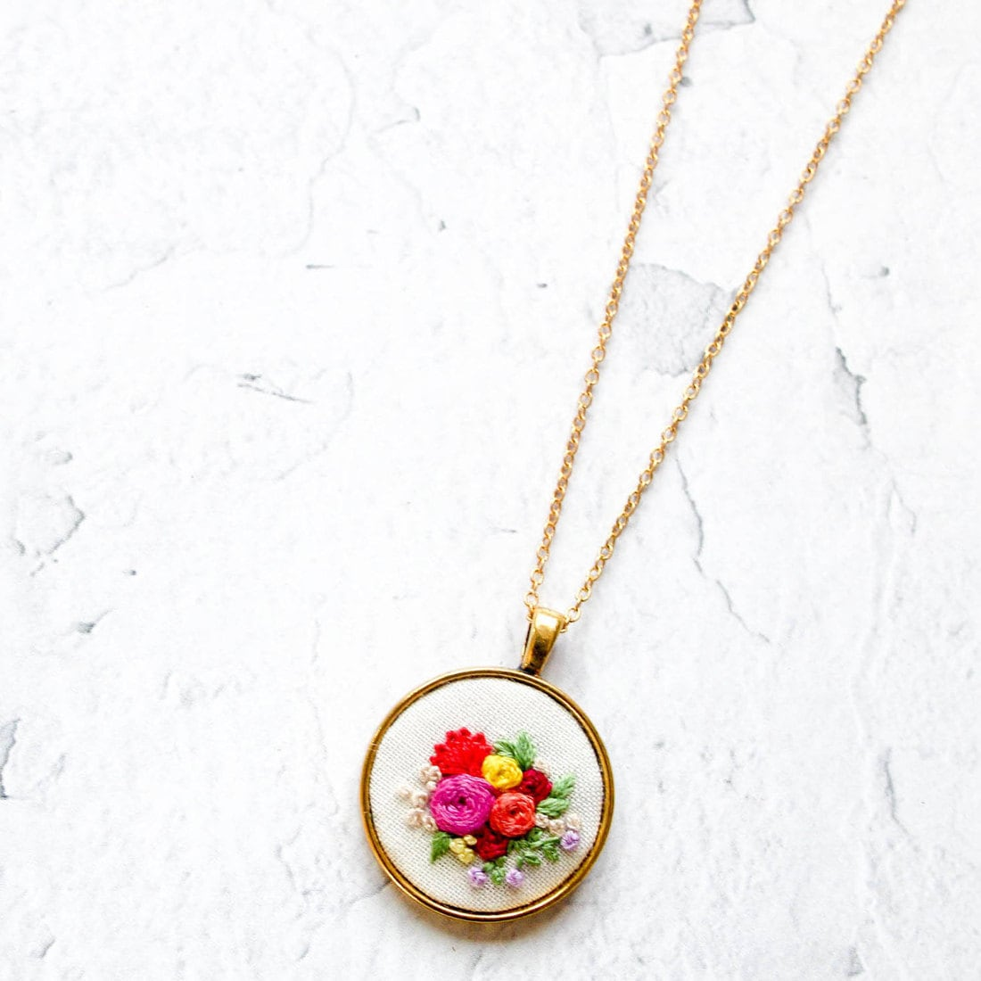 Vibrant floral embroidered necklace set in a circular gold pendant from Thursday Craft Love