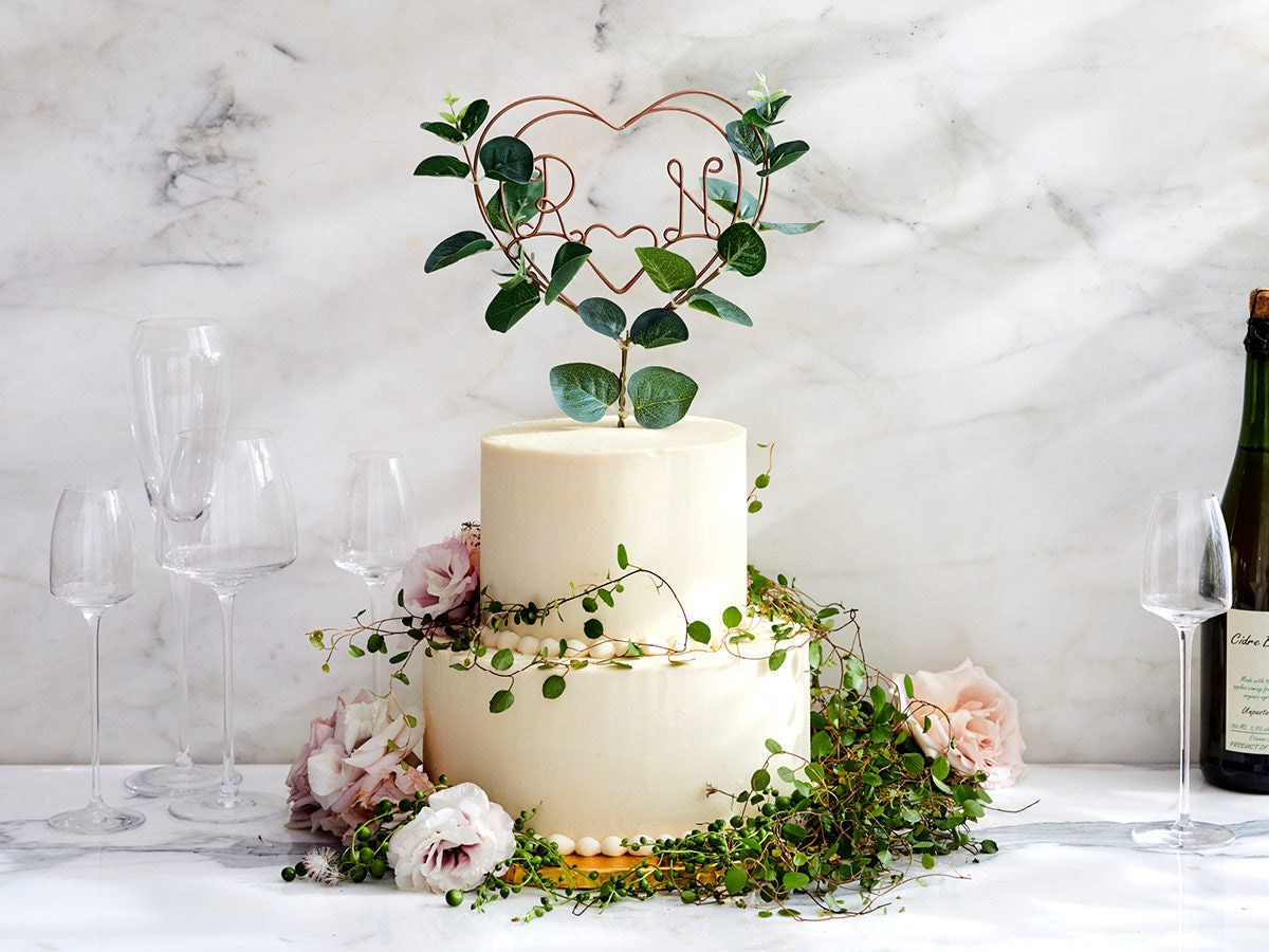 Eucalyptus adorned, heart-shaped wire cake topper from The Letter Loft displayed on a wedding cake