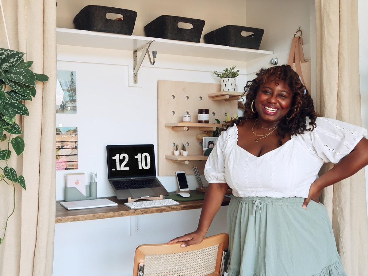 Home and style influencer Janea Brown poses in front of her closet-turned-home office full of fun, functional Etsy finds.