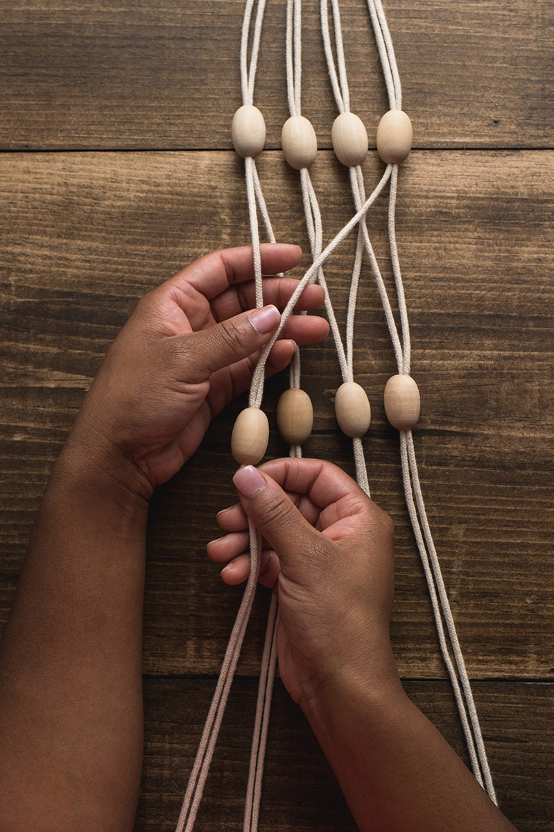 Hands separate the ropes and group into adjacent pairs, adding a bead to each.
