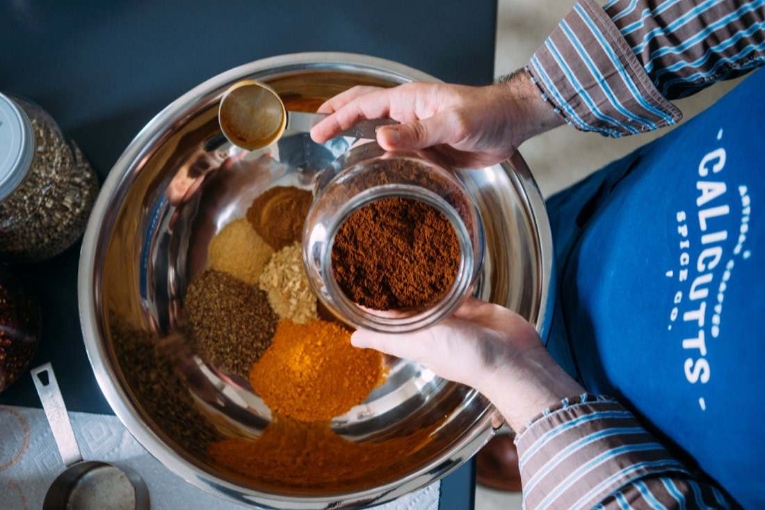 Robert measures out proportions of different ground herbs and spices to make one of his signature blends