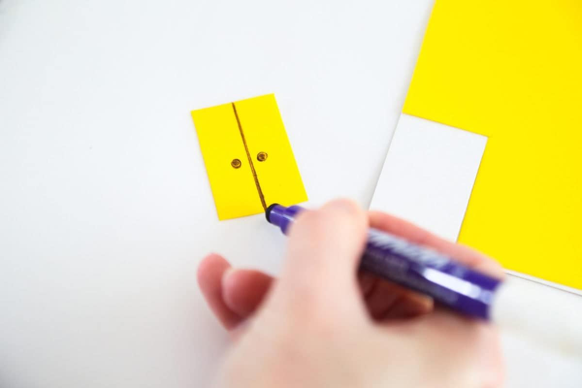 Drawing door details onto a piece of yellow icing.