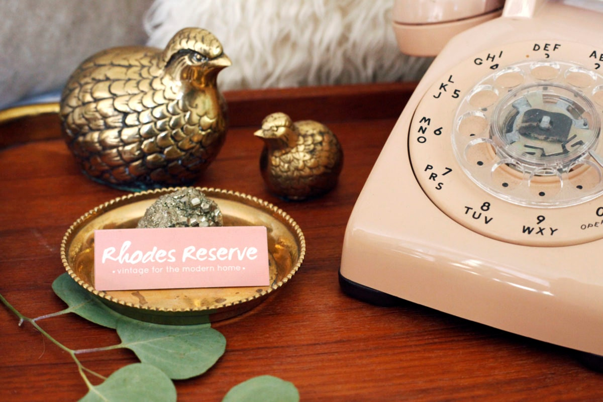 Brass birds, vintage phone, and Rhodes Reserve business cards arranged in Brenda's home