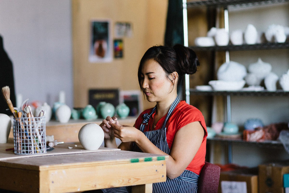 Yumiko at work in her studio, seated at her workbench