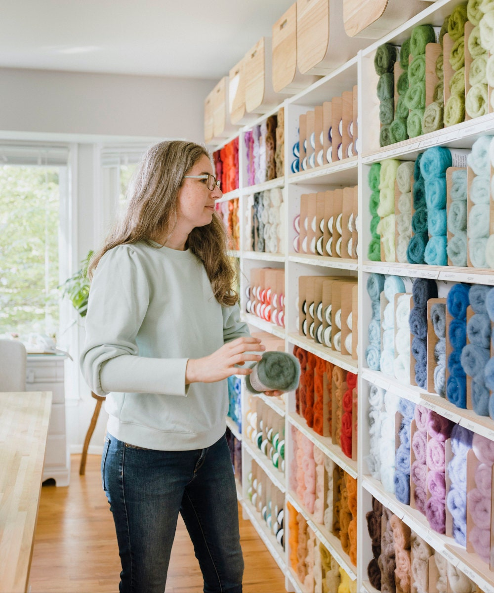 Elizabeth selects some roving from a wall of colored felts.