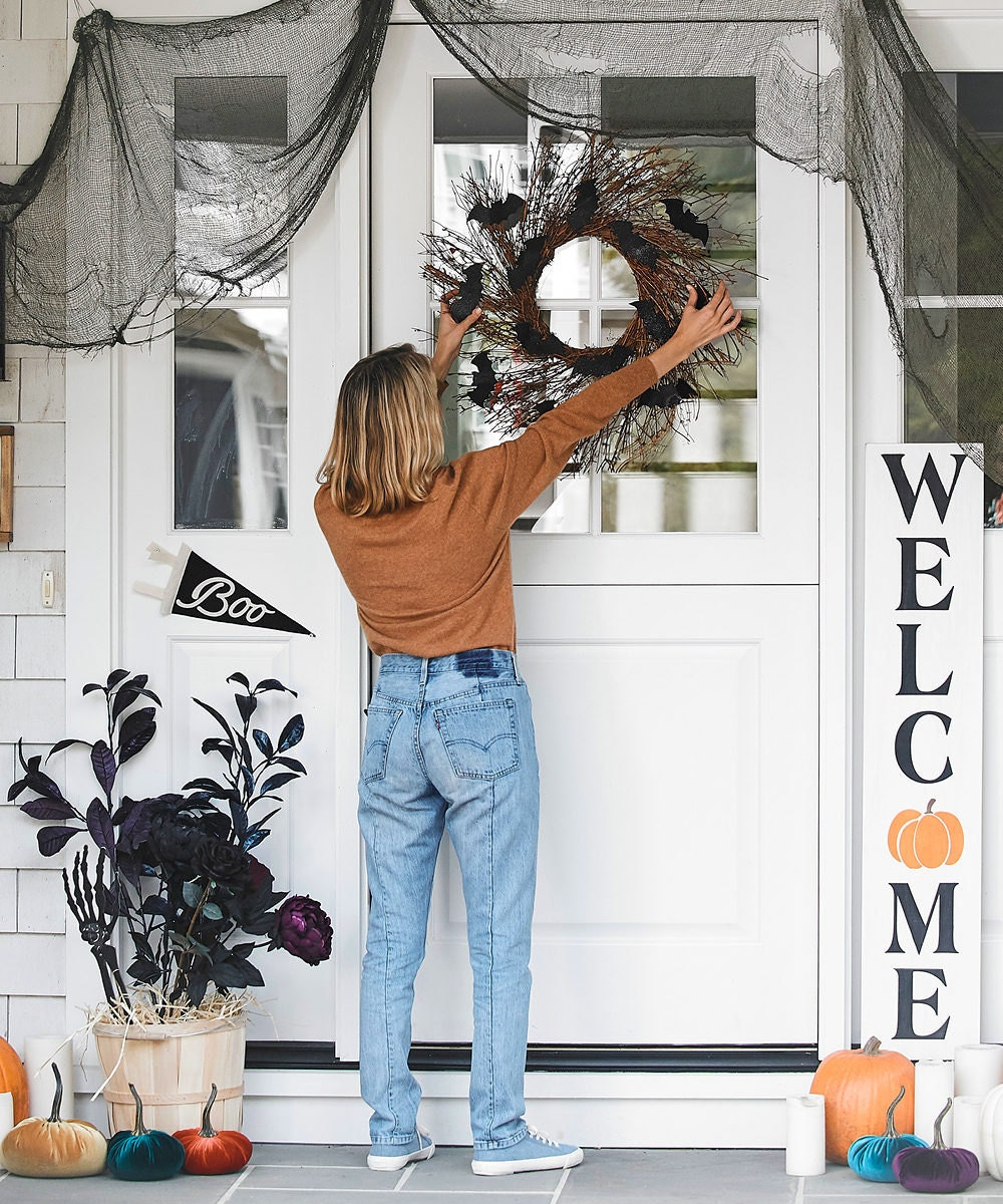 A woman hangs a sparkly bat wreath on the front door of a porch decorated for Halloween