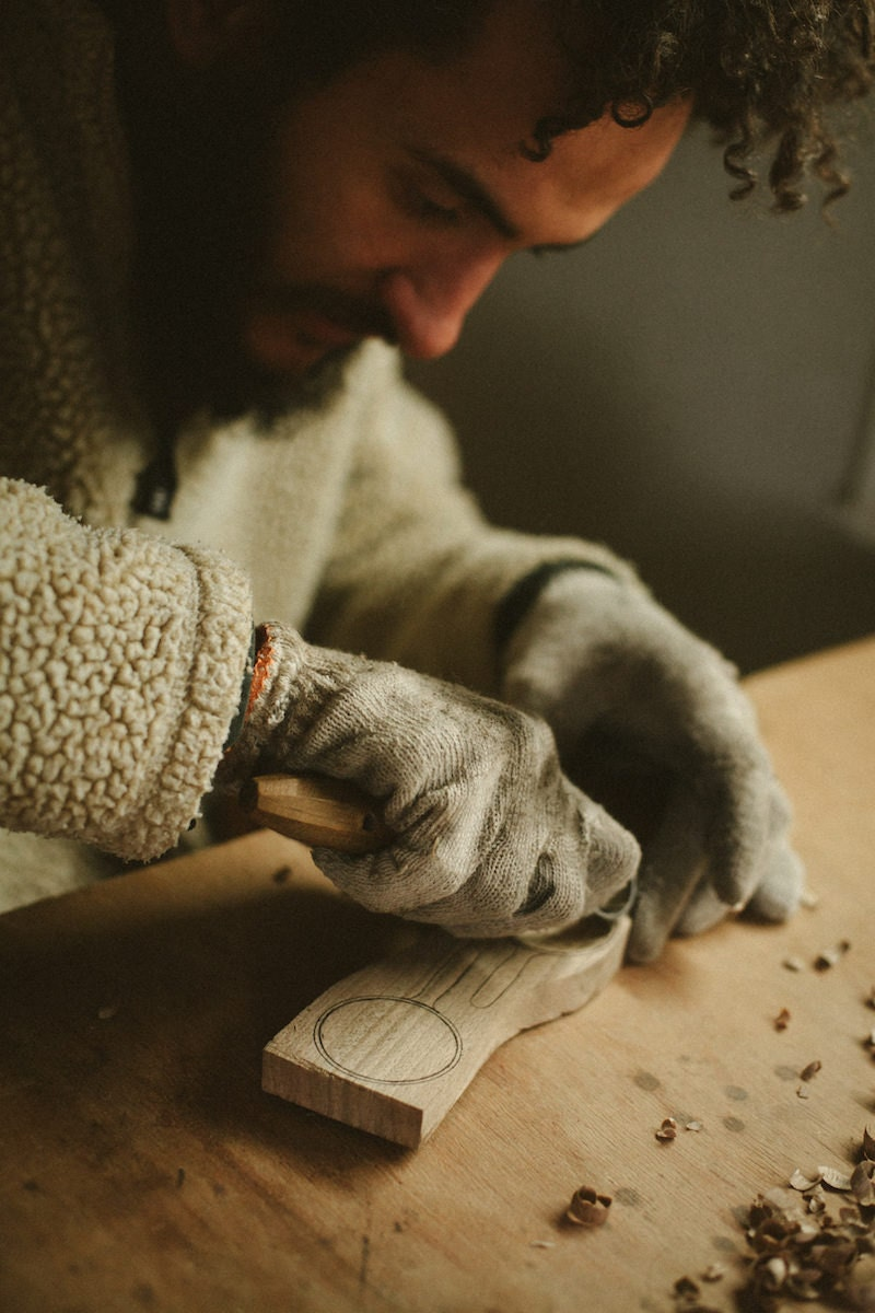 Kirill carves a spoon from a wooden block by hand