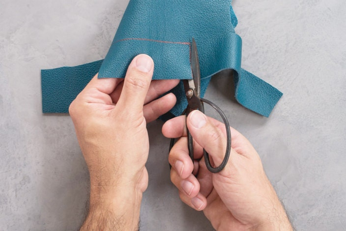 Steel shears cut rectangular strip of leather