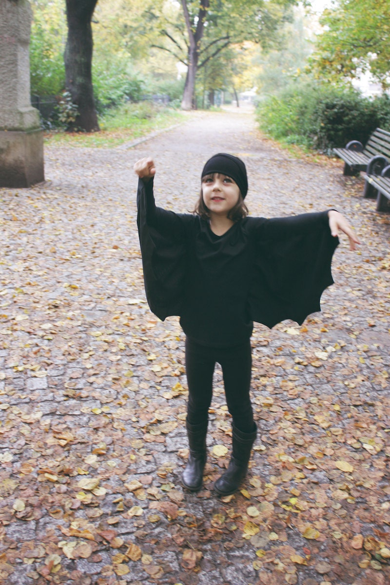 A young child wearing a handmade DIY bat costume for Halloween