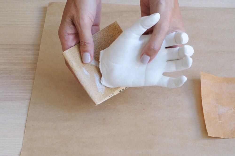Sanding the bottom of the plaster hand