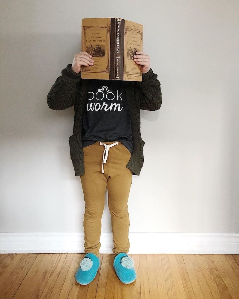 """A child wearing a """"Bookworm"""" T-shirt from Nature Supply Co. holds a book up to his face"""