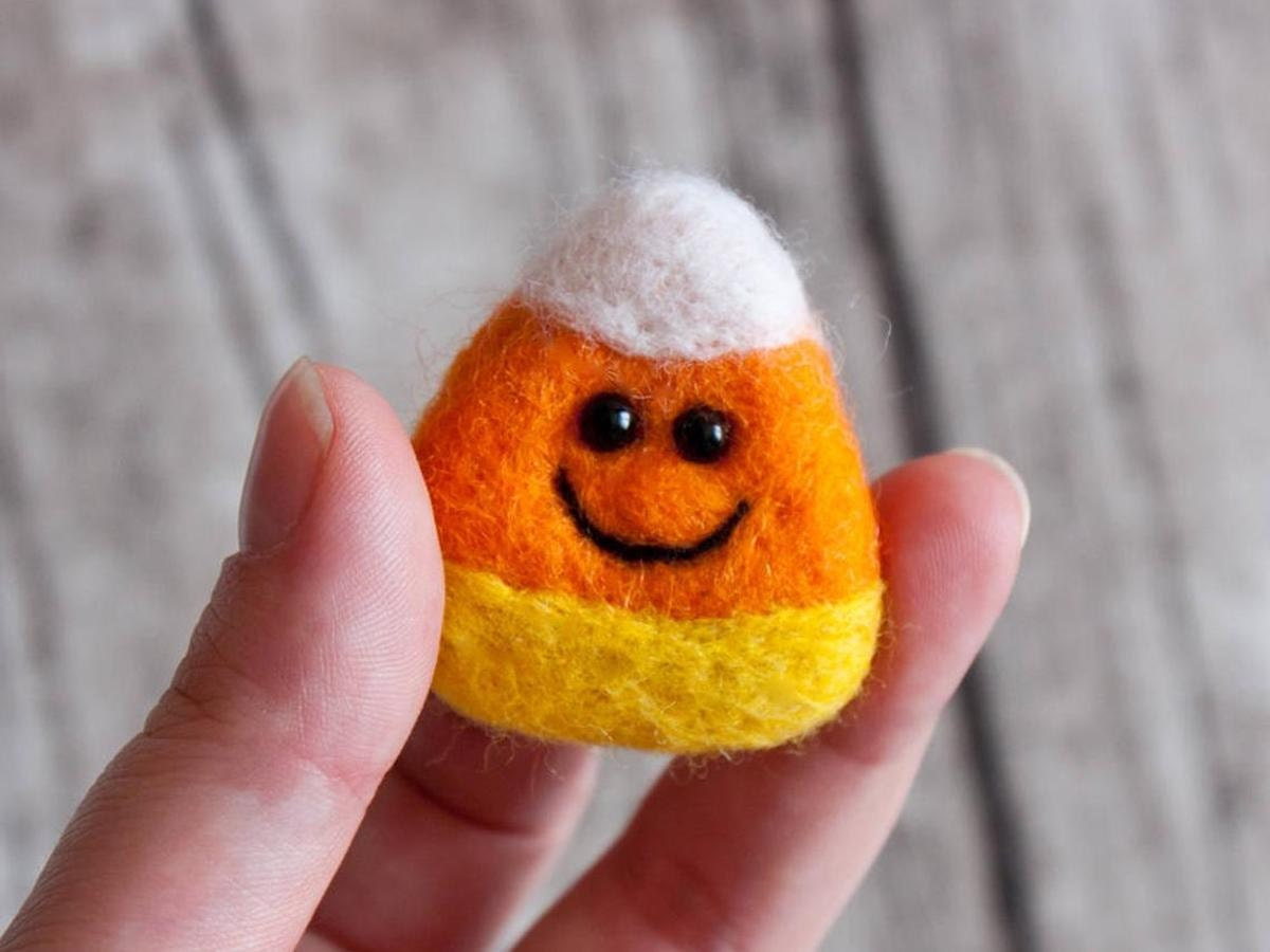 A needle felted candy corn brooch with a smiling face from znmystery.