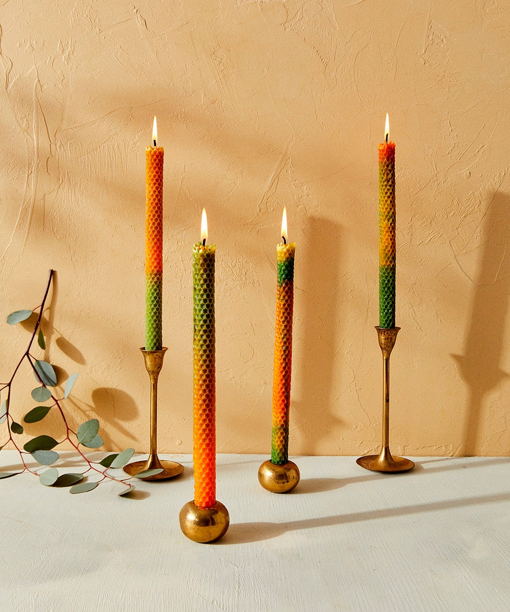 Orange and green taper candles with a honeycomb texture.