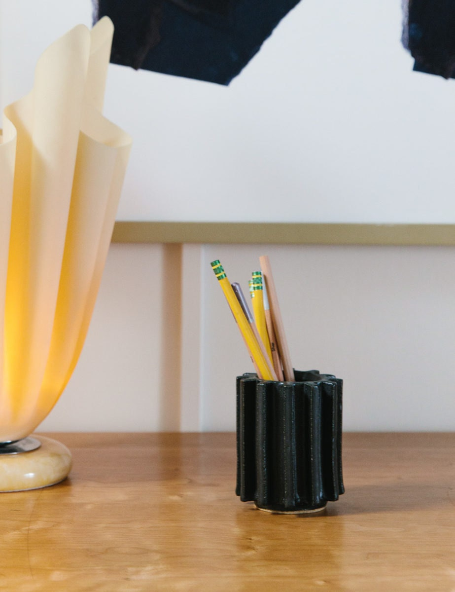A ridged black ceramic cup with number two pencils inside.