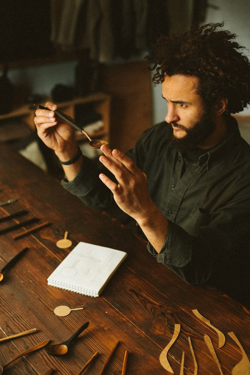 Kirill sits at a table, surrounded by a sketchbook and several finishes pieces, and inspects a wooden spoon