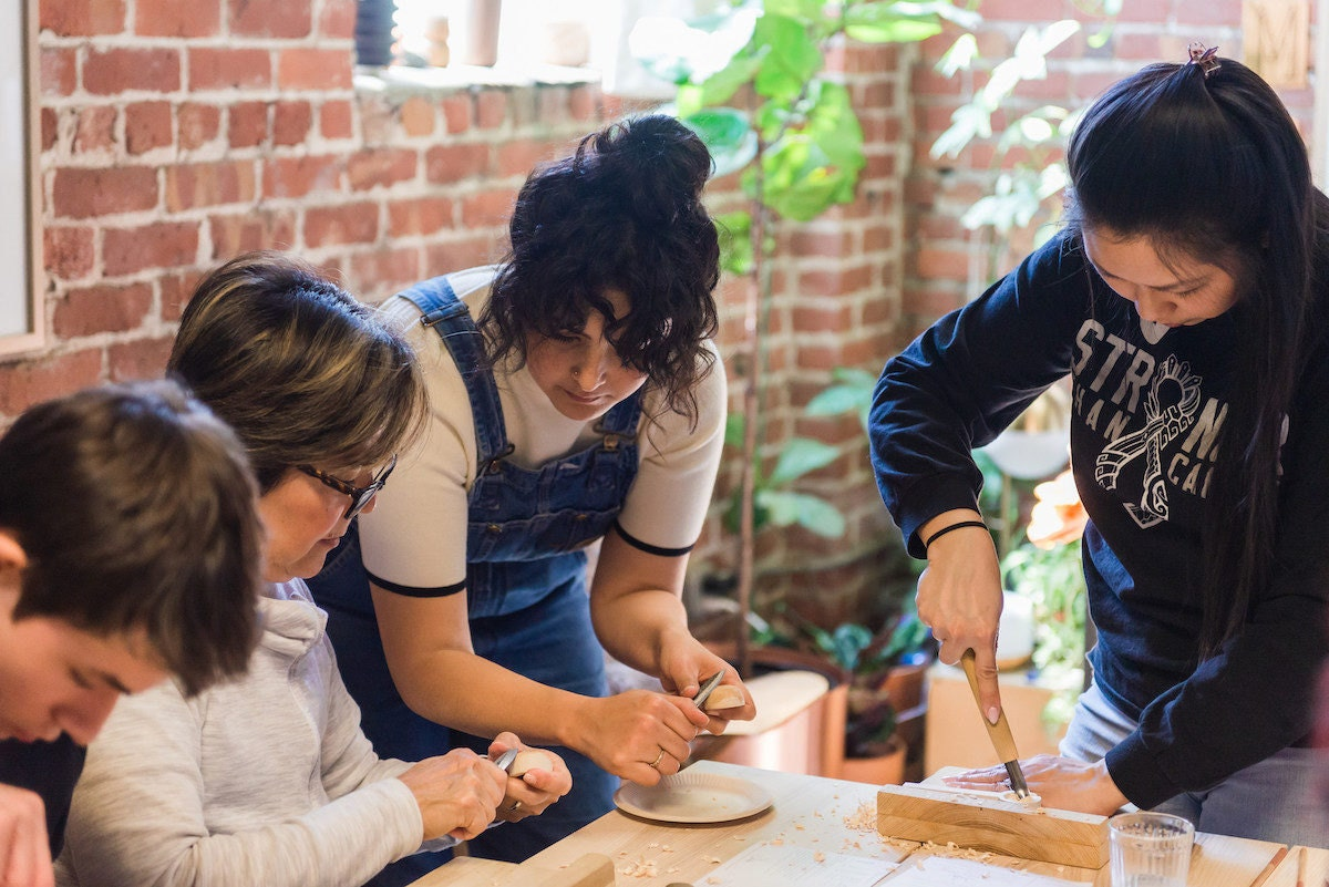 Melanie demonstrates a spoon carving technique at a student workshop