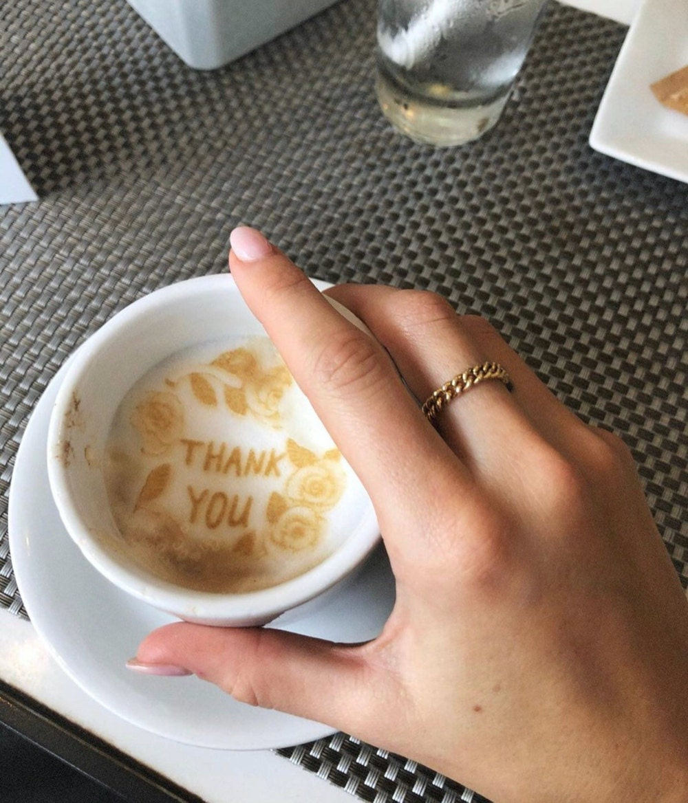 """A hand wearing a gold chain stacking ring holds a coffee cup with the words """"thank you"""" written in the foam."""