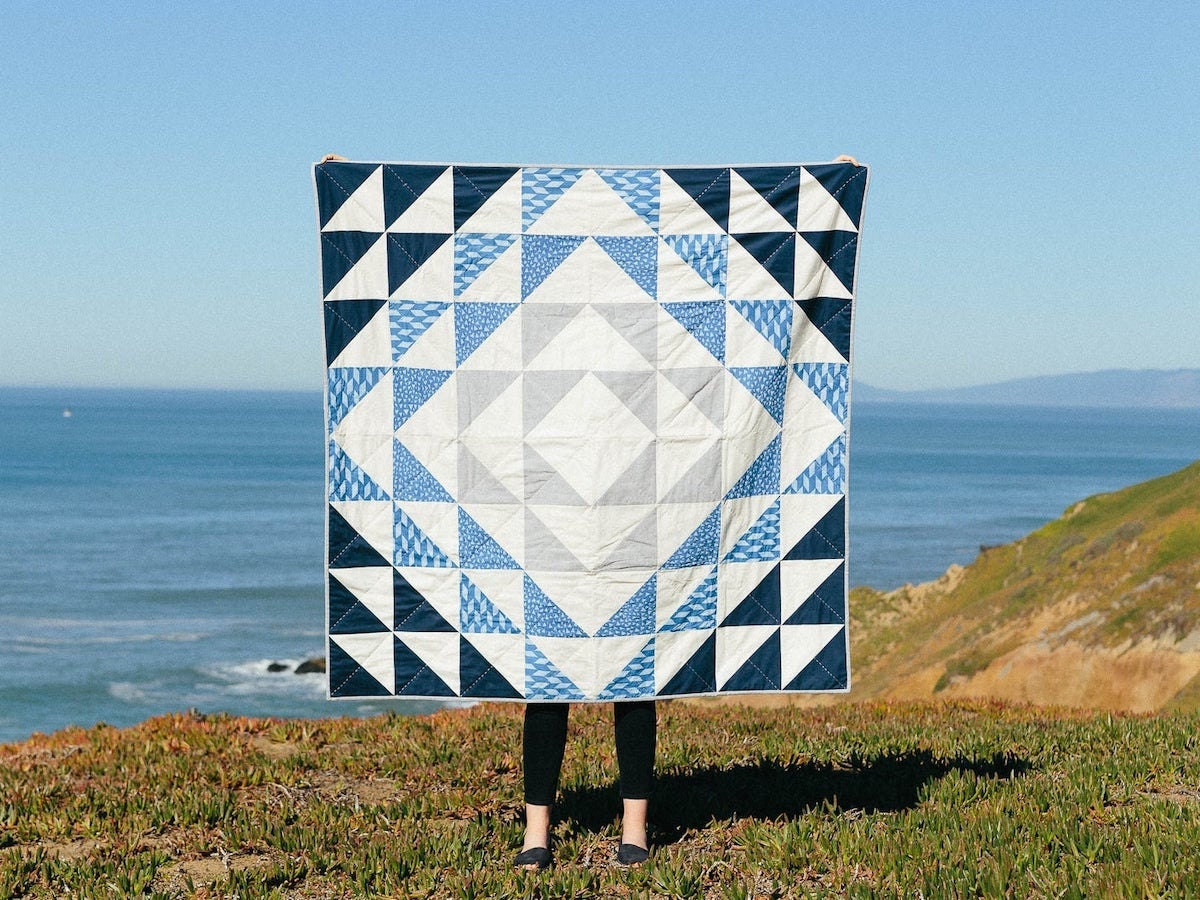 A blue and white quilt held up in front of the ocean