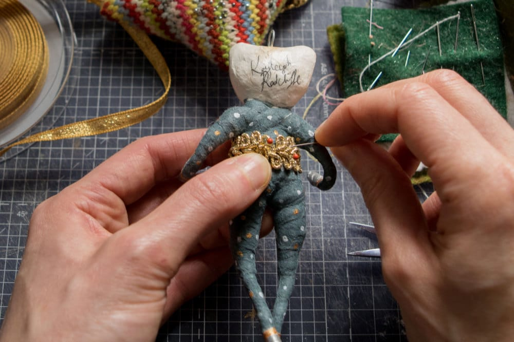 Kayleigh sews an outfit onto her bear ornament
