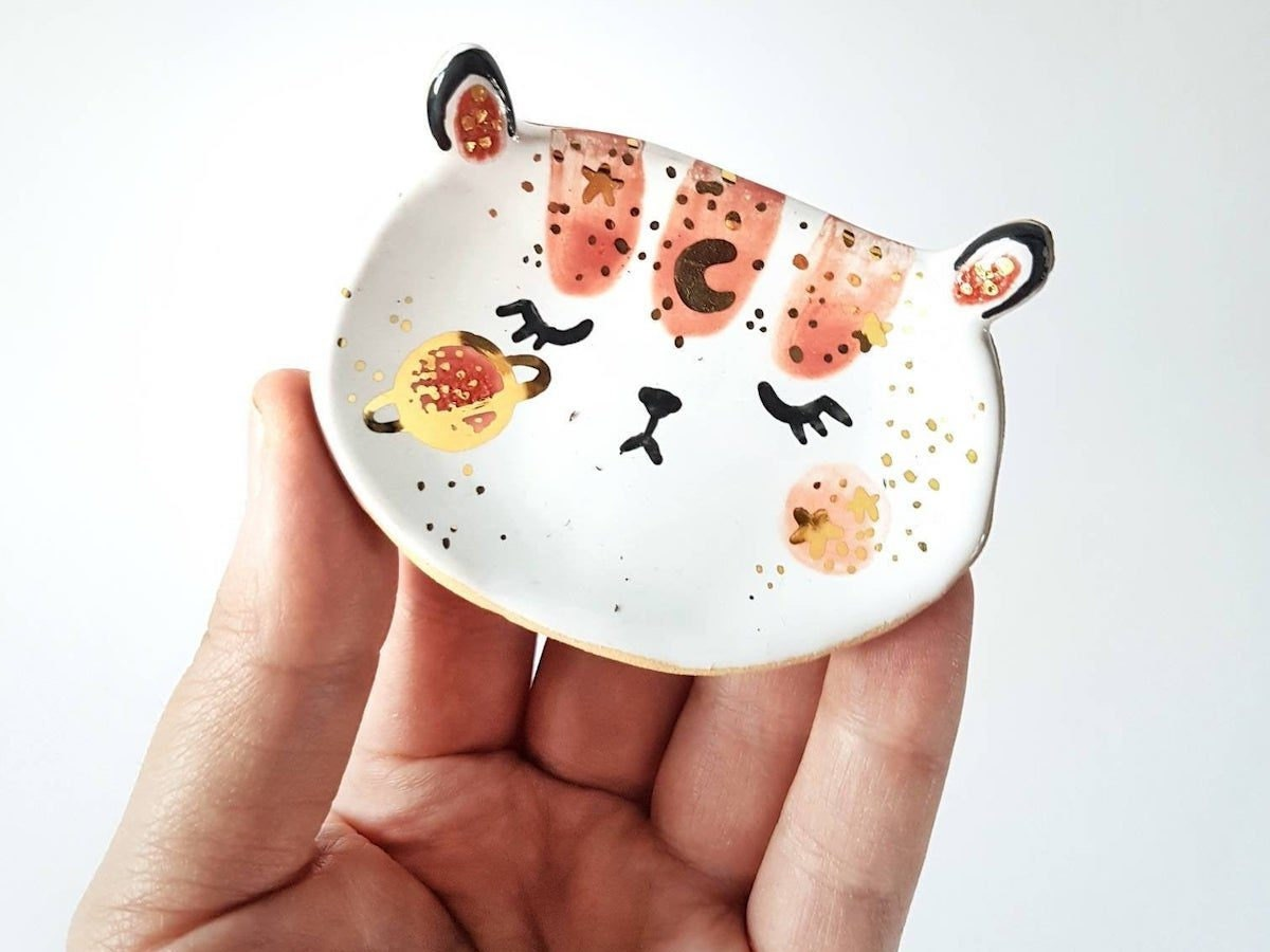 A ceramic, bear-shaped trinket dish painted with moons and planets from Mrs Biscuit Art