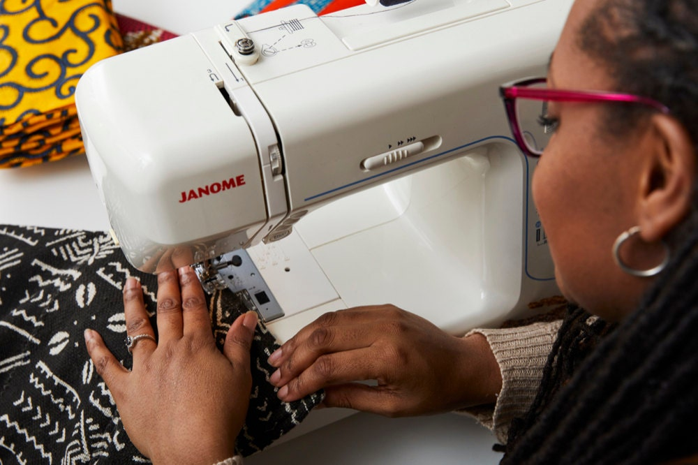 Natalie sews a mud cloth blanket on her sewing machine