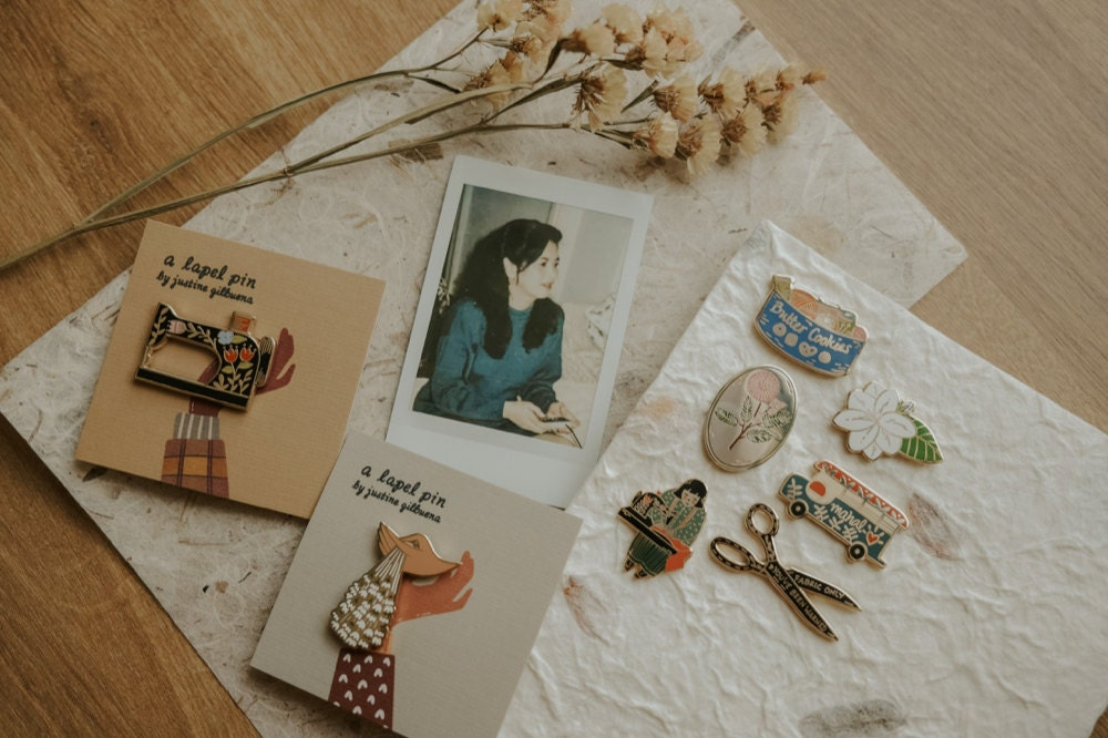 A photograph of Justine's mother pictured alongside a batch of enamel pins inspired by her.