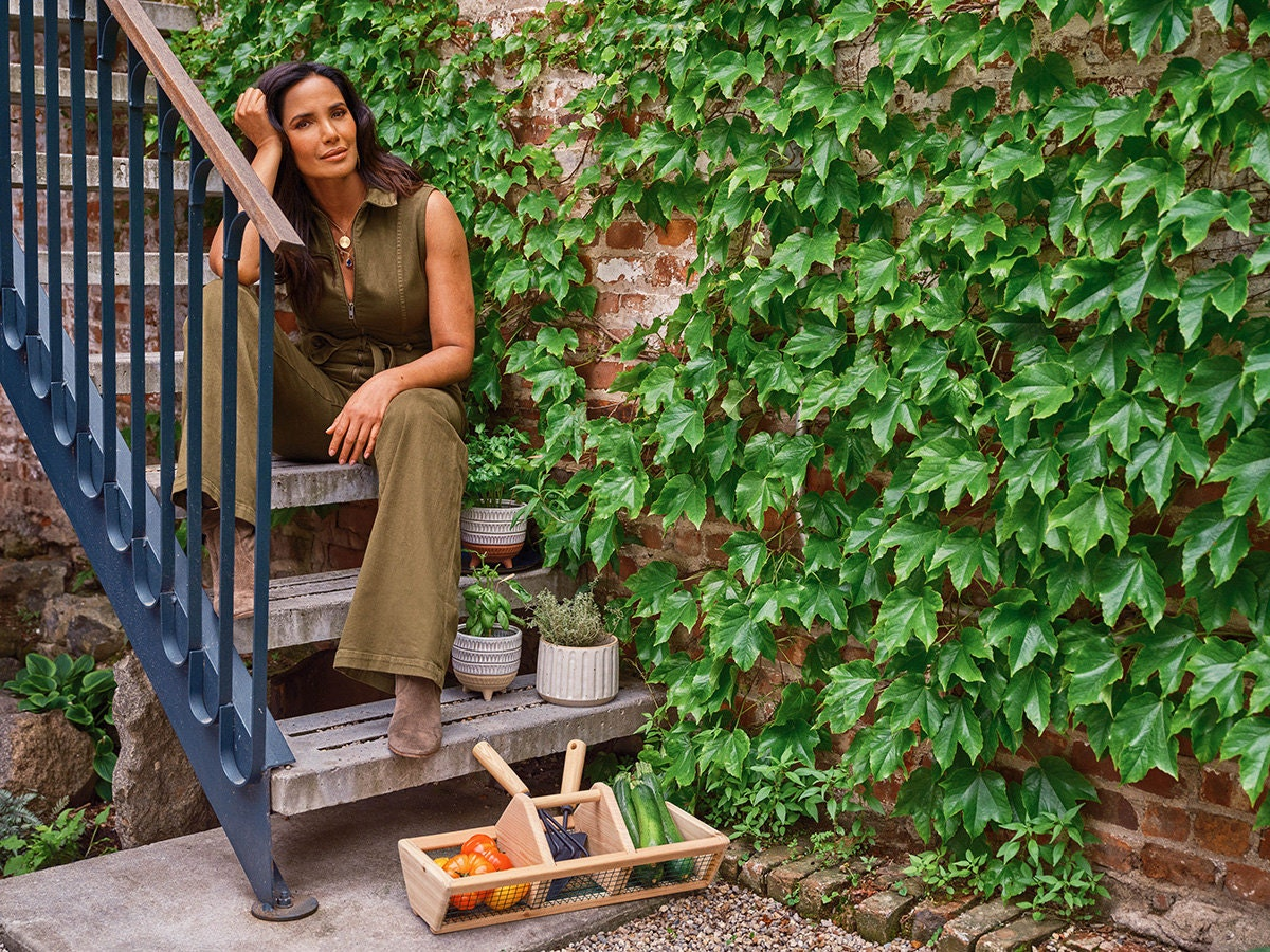 Padma Lakshmi sits on a staircase surrounded by gardening tools and herbs