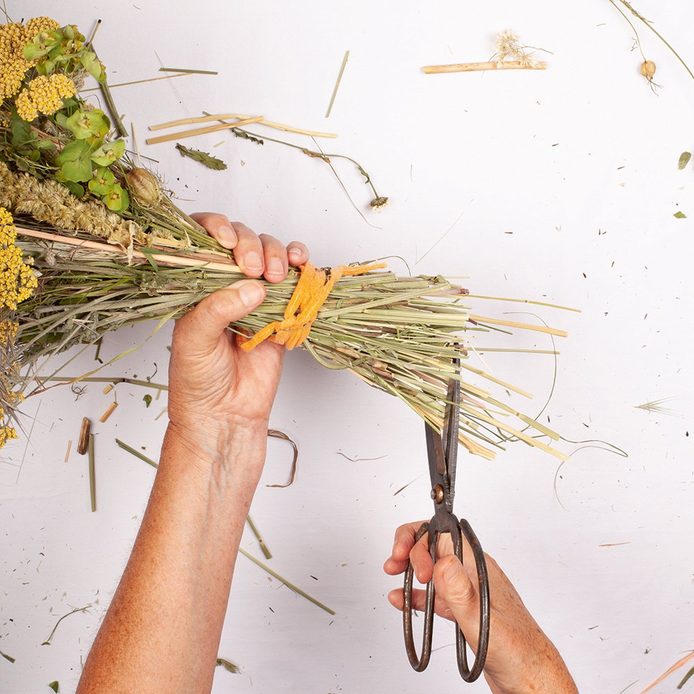 A person completes the final step—trimming the ends of the stems