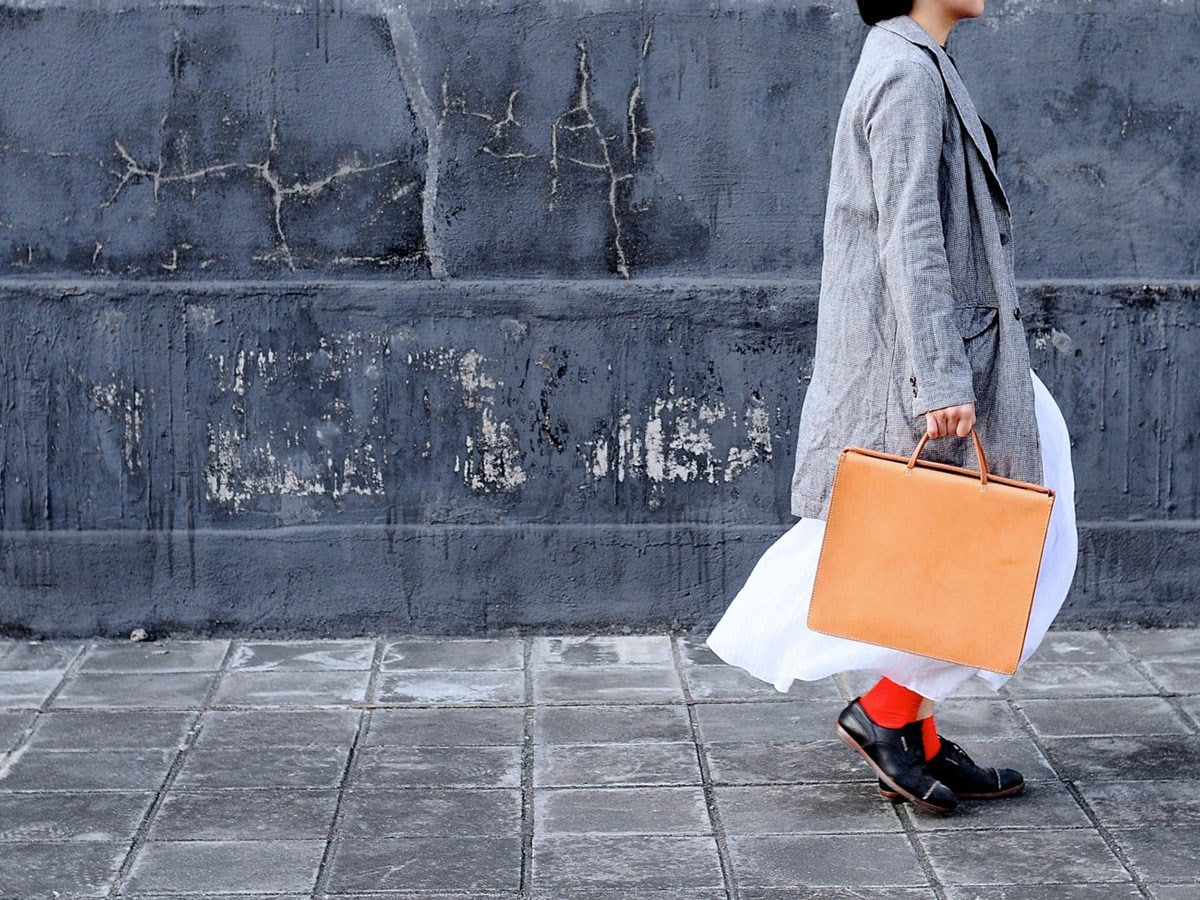 Model carrying a square tan leather bag from Artemis Leatherware